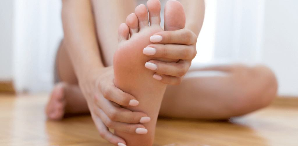 Close up of young woman feeling pain in arch of foot