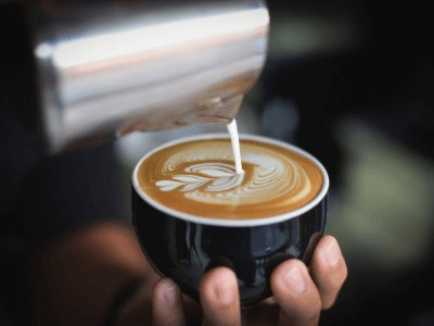 Barista pouring coffee who has foot and back pain at work